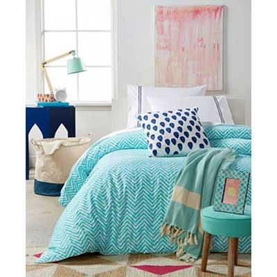 Bedding set with teal duvet cover, decorative pillows, a matching storage bin and picture frame