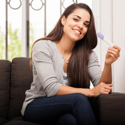 Woman holding positive pregnancy test and smiling
