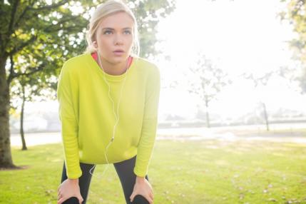Woman in athletic clothes winded from jogging outside