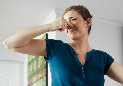 Woman holding nose and grimacing