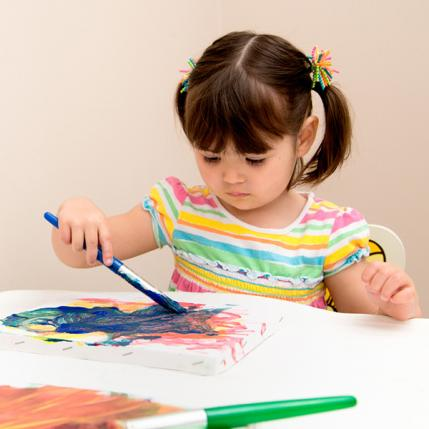 Young girl painting with a paint brush